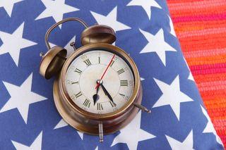 Bigstock-Metal-clock-on-a-dark-blue-pil-69991357